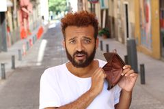 Ethnic broke guy with empty wallet outdoors Stock Photo