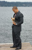 Ethnic Business Man with his Yorkshire Terrier Dog. Ethnic Business Man Making a Sale on Cell Phone holding a calculator while standing by his luxury car at the royalty free stock image
