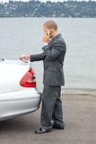 Ethnic Business Man Making a Sale on Cell Phone. Holding a calculator while standing by his luxury car at the lake Royalty Free Stock Photography