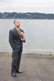 Ethnic Business Man and Yorkshire Terrier Dog. Are standing next to the lake. He is dressed in a suit and tie and seems to be contemplating something Royalty Free Stock Photo