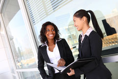 Ethnic Business Woman Team. Two ethnic asian and african business women team at office building Stock Photos