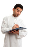 Ethnic businessman working. An ethnic businessman in traditional clothing, holding a clipboard folder and writing with a pen.  White background Royalty Free Stock Image