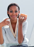 Ethnic businesswoman eating donuts Royalty Free Stock Photography