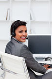 Ethnic businesswoman with headset on. At work royalty free stock photo