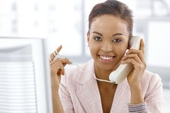 Ethnic businesswoman on landline call. Portrait of smiling ethnic businesswoman on landline phone call, looking at camera Royalty Free Stock Images