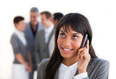 Ethnic businesswoman on phone in front of her team Stock Image