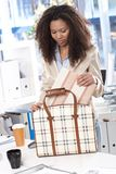Ethnic businesswoman unpacking bag at office Stock Photos