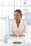Ethnic businesswoman working at desk Stock Photo