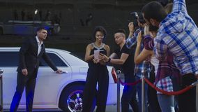 Ethnic celebrity woman on red carpet. African-American famous women walking out of limousine and giving autograph to fan on red carpet of celebrity event stock photo