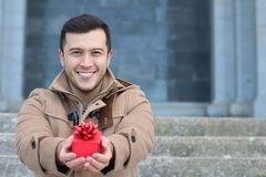 Ethnic cheerful male holding a present stock photo