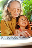 Ethnic child and grandmother playing piano Stock Photography