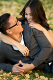 Ethnic couple. Ethnic young couple sitting in a pile of leaves royalty free stock photos