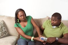 Ethnic couple fighting over TV remote control Royalty Free Stock Photography