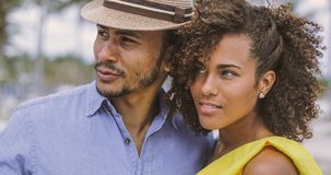 Ethnic couple looking away. Ethnic young handsome men and pretty women standing together in the park and looking away royalty free stock image