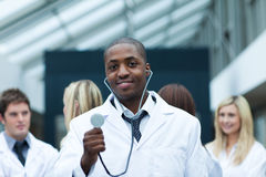 Ethnic doctor with his team in the background Stock Images