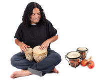 Ethnic drummer. Funky long haired ethnic African American and Native Indian male playing bongo drums on a white background with other latin instruments to the Stock Photos