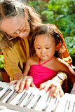 Ethnic elderly woman teach child play piano. Asian ethnic grandmother teach child playing piano royalty free stock photos