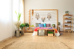 Bedroom with rug and shelves. Ethnic ethereal bedroom with colorful bed and a wicker rug and wooden shelves Royalty Free Stock Photo