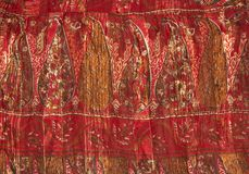 Ethnic fabric. Closeup of ethnic fabric in warm red tones royalty free stock image