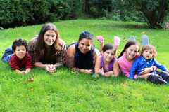 Ethnic family. Mixed race beautiful ethnic family with parents and four children laying on the grass Stock Photo