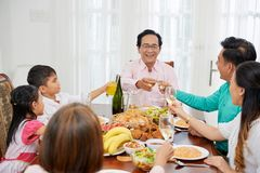 Ethnic family clinking with glasses at table. Adult Asian people with children gathering at table at home while toasting with glasses and having celebration royalty free stock photos