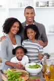 Ethnic family preparing salad together. In the kitchen Stock Image