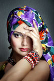 Ethnic fashion portrait. Fashion portrait of girl in ethnic vivid head scarf and bracelet with hand closing one eye, selective focus stock photos
