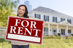 Ethnic Female Holding For Rent Sign In Front of House. Excited Mixed Race Female Holding For Rent Sign In Front of Beautiful House stock photo