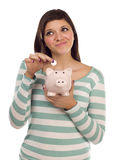 Ethnic Female Putting Coin Into Piggy Bank stock photo