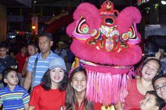 Ethnic Filipino Chinese Pose with Dancing Lion Mascot during New Year Celebration on the street. Manila, Philippines - February 7, 2016: Ethnic Filipino Chinese Royalty Free Stock Photos