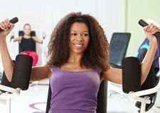 Ethnic girl exercising at the gym. Pretty ethnic girl exercising at the gym on weight machine, smiling Royalty Free Stock Photography