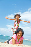 Ethnic girl fun with mother on tropical beach Stock Image
