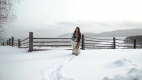 Ethnic girl with long hair sneaks through the drifts. In the background is a wooden fence and mountains. Snowing.  stock video footage