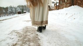 Ethnic girl walking on a snow-covered road. Culture. North. Very long hair stock video