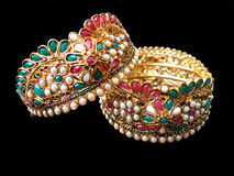 Ethnic Gold Bangles. A beautiful pair of bangles with pearls,gems and meena specially design by indian jewelers Stock Image