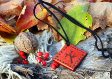 Ethnic handmade magic red clay amulet. On autumn-style background stock photos
