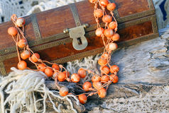 Ethnic handmade woodeny necklace and old wooden chest. Ethnic handmade wooden necklace and old wooden chest on autumn-style background Stock Photo