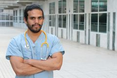 Ethnic health care worker posing confident with arms crossed - Stock image with Copy Space.  Stock Photo