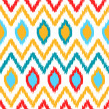 Ethnic ikat abstract colorful geometric pattern in white, yellow, red and blue, vector Royalty Free Stock Image