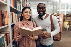 Ethnic indian mixed race girl and black guy in library. Students are looking for books. Ethnic indian mixed race girl and black guy surrounded by books in Stock Photo