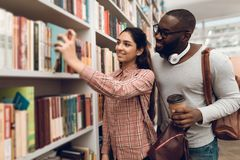 Ethnic indian mixed race girl and black guy in library. Students are looking for books. Ethnic indian mixed race girl and black guy surrounded by books in Royalty Free Stock Images