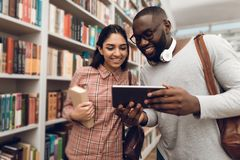 Ethnic indian mixed race girl and black guy in library. Students are using tablet. Ethnic indian mixed race girl and black guy surrounded by books in library Stock Photography
