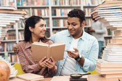 Ethnic indian mixed race girl and guy surrounded by books in library. Students are reding book. Ethnic indian mixed race girl and guy sitting at table Stock Images