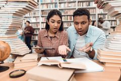 Ethnic indian mixed race girl and guy surrounded by books in library. Students are taking notes. Ethnic indian mixed race girl and guy sitting at table Royalty Free Stock Photography