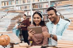 Ethnic indian mixed race girl and guy surrounded by books in library. Students are using tablet. Ethnic indian mixed race girl and guy sitting at table Royalty Free Stock Image