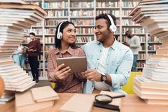 Ethnic indian mixed race girl and guy surrounded by books in library. Students are using tablet. Ethnic indian mixed race girl and guy sitting at table Royalty Free Stock Images