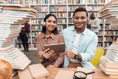 Ethnic indian mixed race girl and guy surrounded by books in library. Students are using tablet. Ethnic indian mixed race girl and guy sitting at table Stock Images