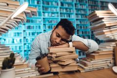 Ethnic indian mixed race guy surrounded by books in library. Student is sleeping. Ethnic indian mixed race guy sitting at table surrounded by books in library Royalty Free Stock Photos