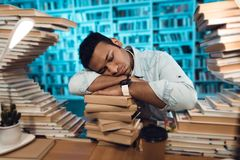 Ethnic indian mixed race guy surrounded by books in library. Student is sleeping. Ethnic indian mixed race guy sitting at table surrounded by books in library Royalty Free Stock Images