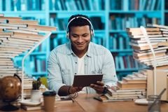 Ethnic indian mixed race guy surrounded by books in library. Student is using tablet. Ethnic indian mixed race guy sitting at table surrounded by books in Royalty Free Stock Photo
